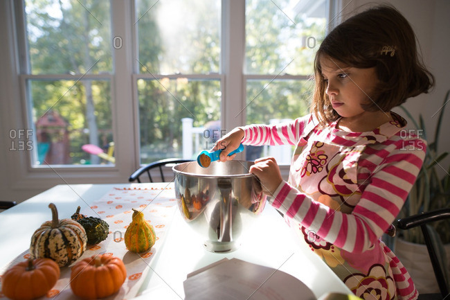 Girl adding ingredients to a bowl at the kitchen table