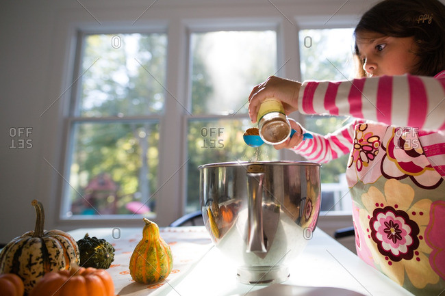 Girl measuring ingredients over a mixing bowl at the kitchen table