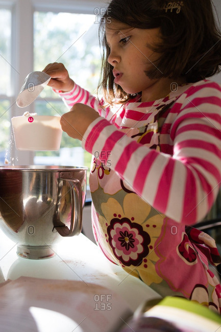 Girl measuring ingredients over a bowl at the kitchen table