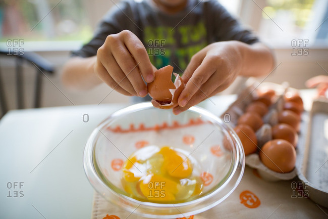 Close-up of a child cracking an egg over a bowl at the kitchen table