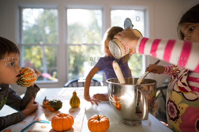 Girl pouring pumpkin mix into a mixing bowl at the kitchen table
