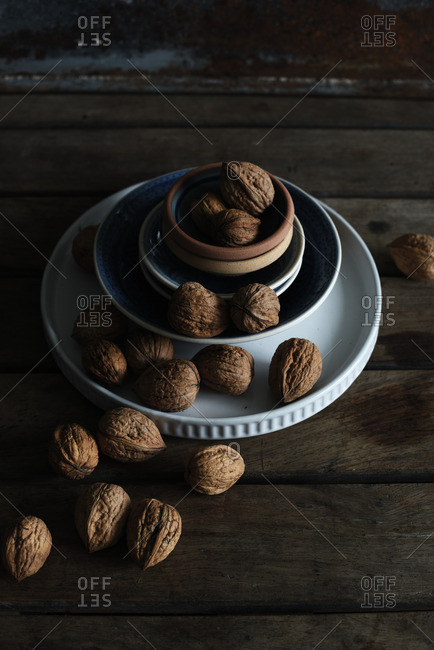 Walnuts on a wooden table with stacked bowls
