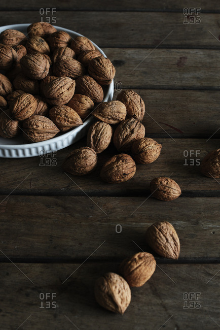 Walnuts on a wooden table in and around a white dish