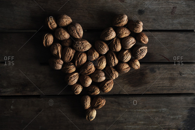Close up of walnuts on a wooden table shaped as a heart