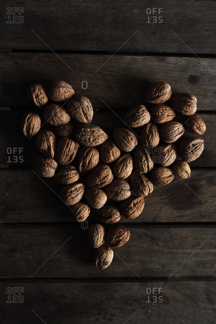 Walnuts on a wooden table shaped as a heart
