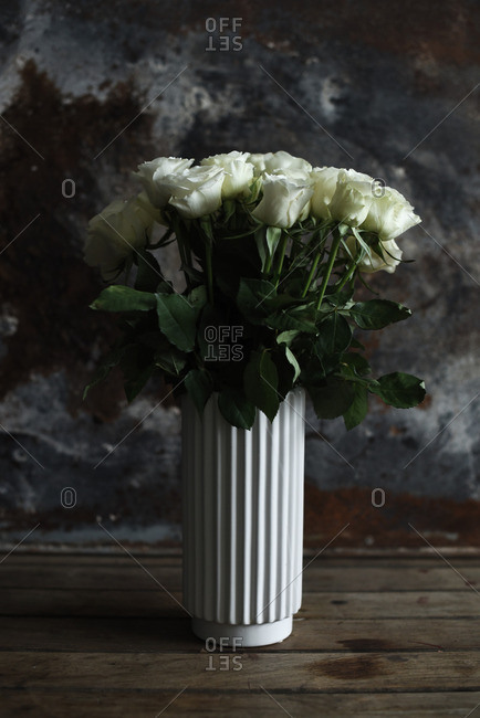 White roses in a white vase on a dark rustic background
