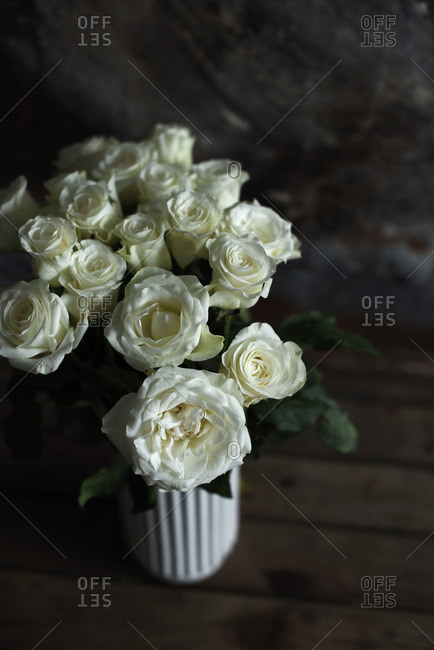 High angle view of white roses in a white vase on a wooden table