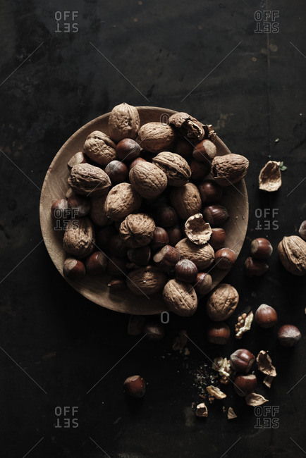 Walnuts and hazelnuts on a wooden plate on a black table