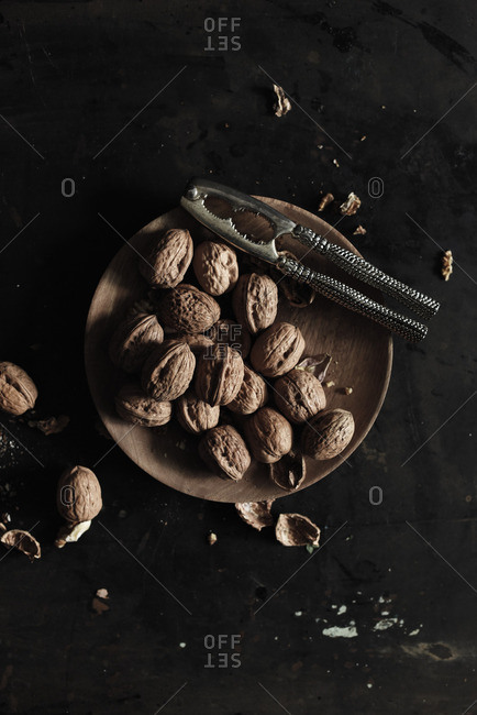 Overhead view of plate of walnuts on a black table