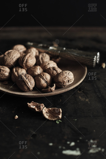 Wooden plate of walnuts on a black table