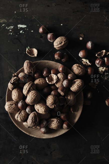 Overhead view of plate of walnuts and hazelnuts on black table