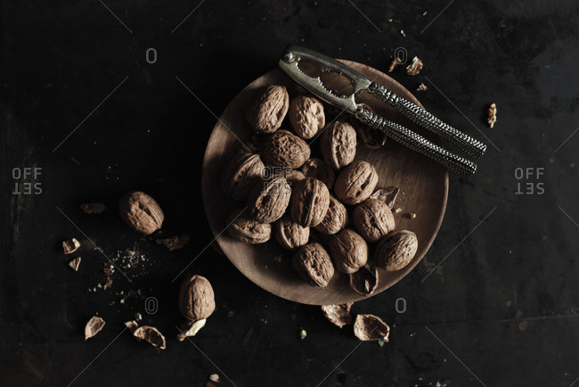 Wooden plate of walnuts with nutcracker on black table