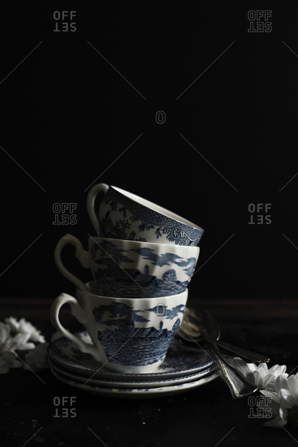 Stack of vintage teacups with flowers on black background
