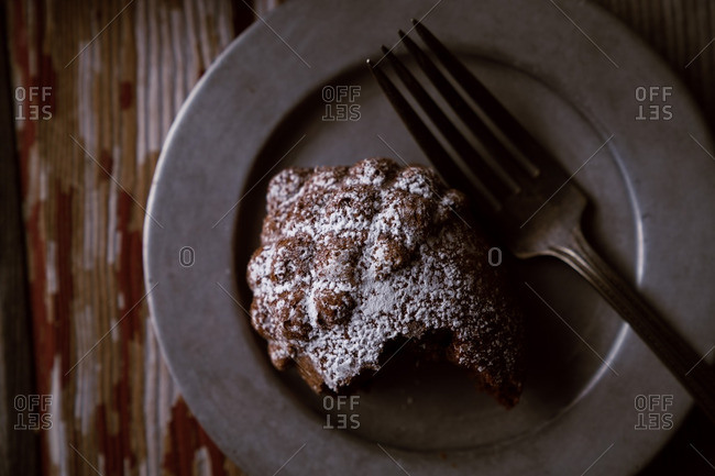Acorn-shaped cake with powdered sugar on plate with fork