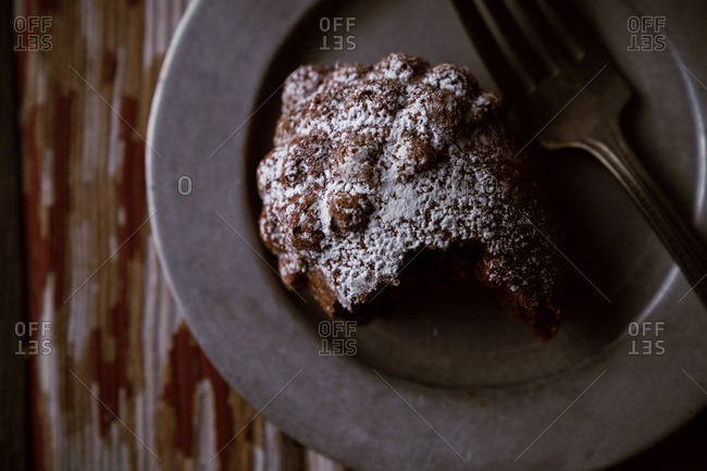 Close-up of a half-eaten acorn cake with powdered sugar