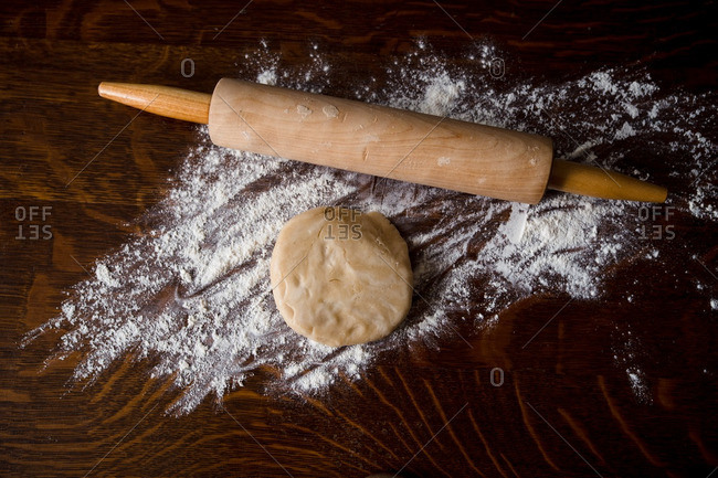 Ball of dough on wooden table with flour and rolling pin