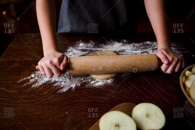 Person using rolling pin to roll out pie dough