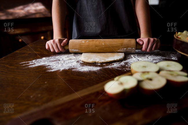 Person rolling out pie crust on wooden table