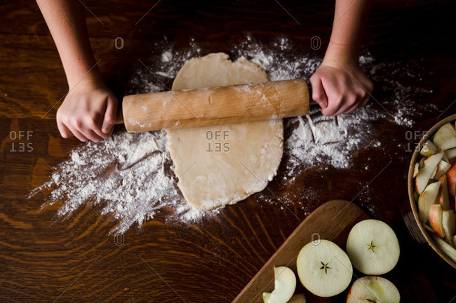 Person using rolling pin to flatten pie crust dough