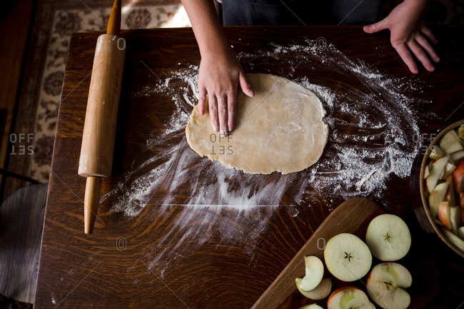 Pressing out pie crust dough for apple pie