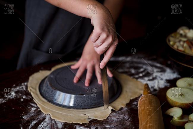 Cutting dough around pie pan