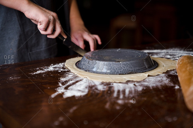Person trimming pie crust dough around pan