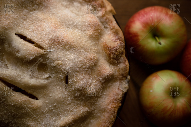 Overhead view of homemade apple pie with fresh apples