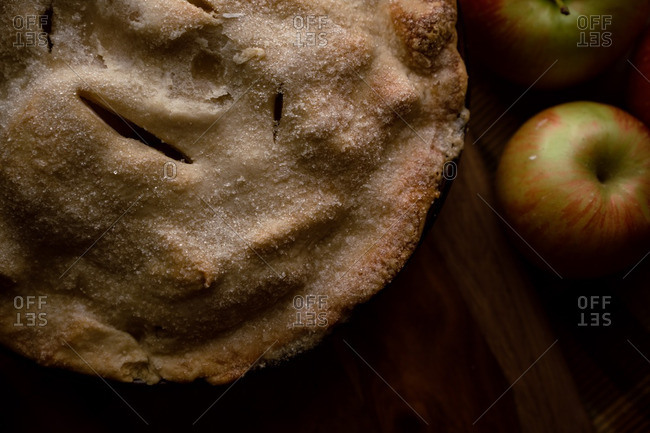 Close-up of top of apple pie with fresh apples