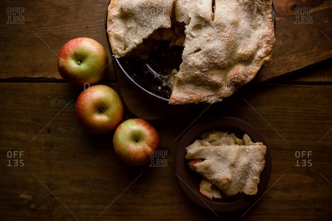 Apple pie with slice removed and three apples
