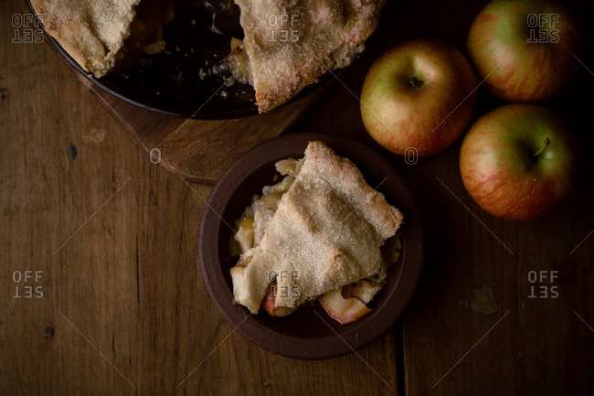 Overhead view of a slice of apple pie with fresh apples
