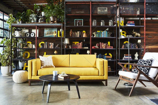 Los Angeles, United States - March 8, 2016: Yellow sofa, retro chair and tall open bookshelves