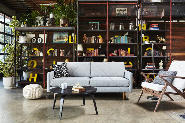Los Angeles, United States - March 8, 2016: Modern gray sofa, retro chair and tall open bookshelves