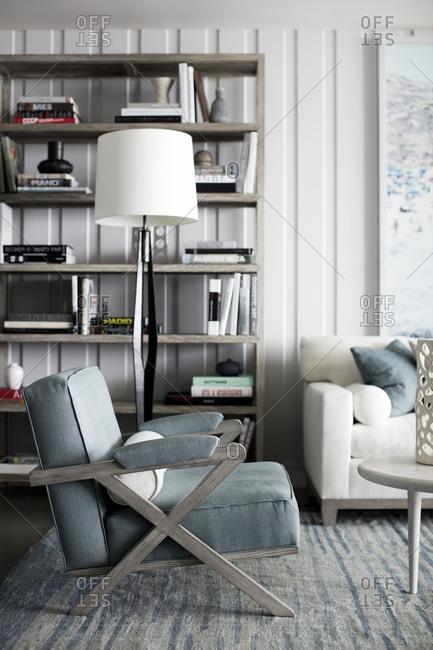 September 22, 2015: Armchair, lamp and bookshelf in a modern living room
