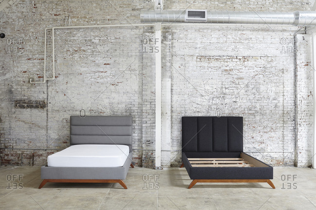 Gray and black platform beds against a brick industrial wall