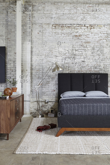 Black platform bed, console and lamp against an industrial brick wall