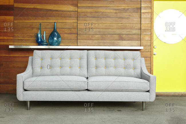 Gray tufted sofa with yellow buttons against a wood wall
