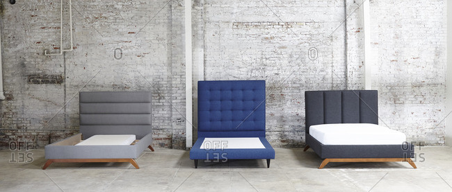 Three upholstered bed frames against an industrial brick wall