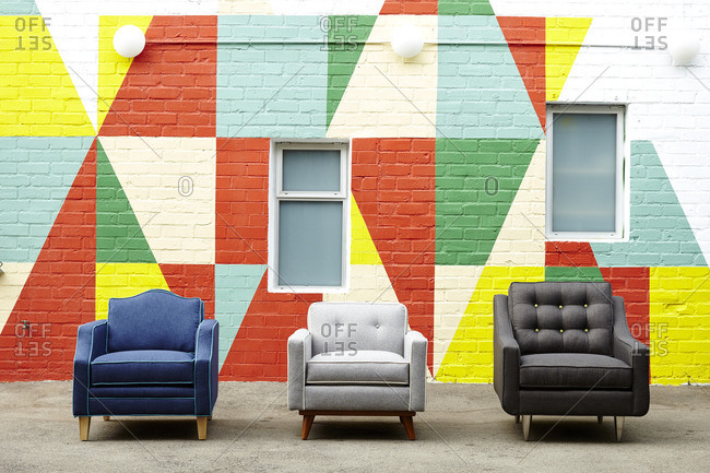 Three armchairs in front of a brightly painted geometric wall