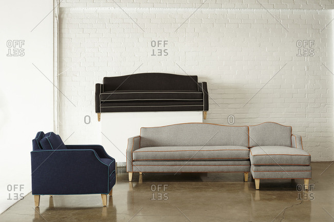 Sofas with contrasting piping on display in front of a painted brick wall