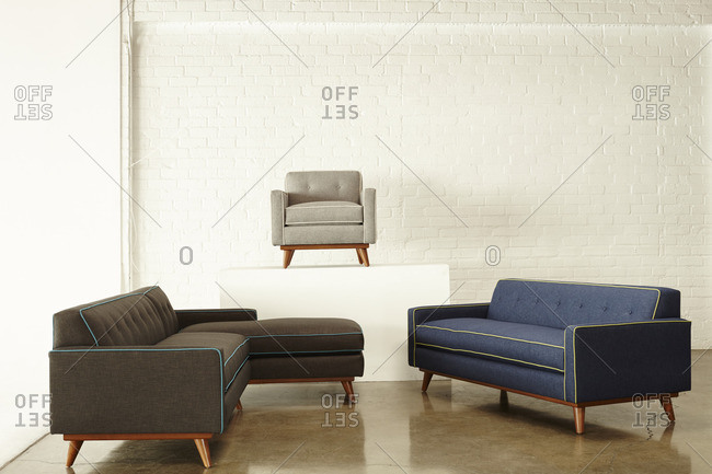 Sofas and chair with contrasting piping on display