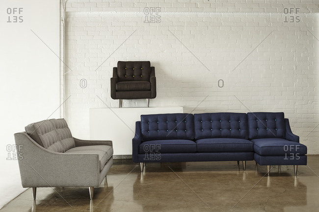 Tufted sofas and chair on display in front of a brick wall