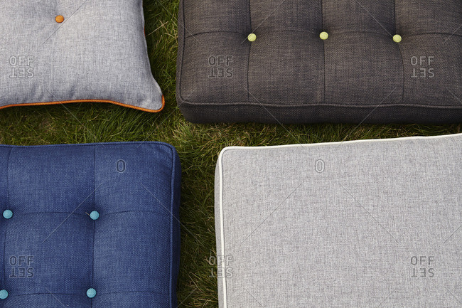 Tufted, upholstered cushions and pillows on a lawn