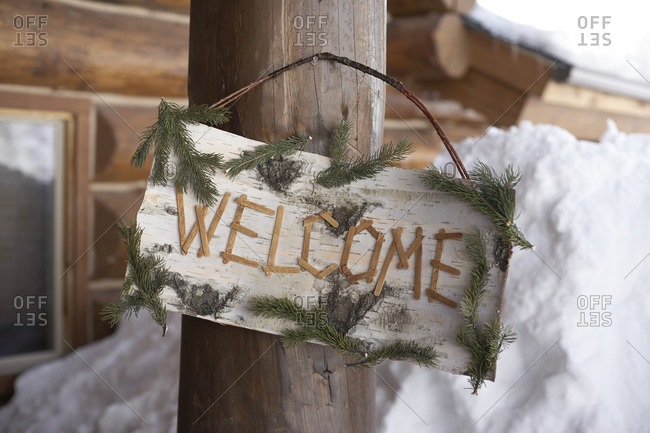 Welcome sign hanging on the post of a log cabin