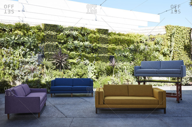 Modern sofas on display in front of a tiered garden