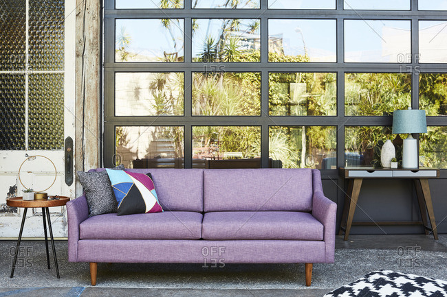 Lavender sofa in front of a wall of exterior windows