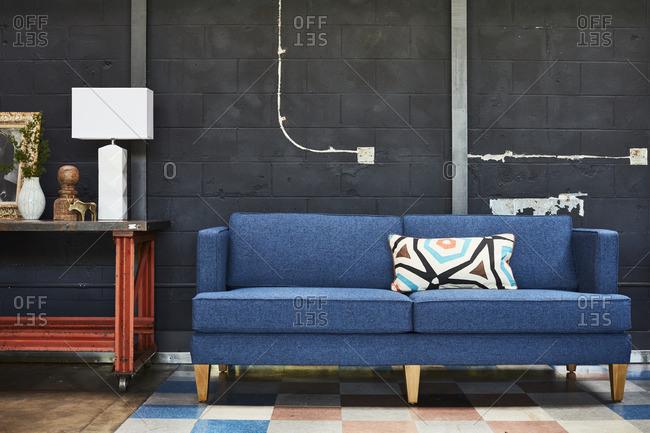Modern blue sofa against an industrial black wall
