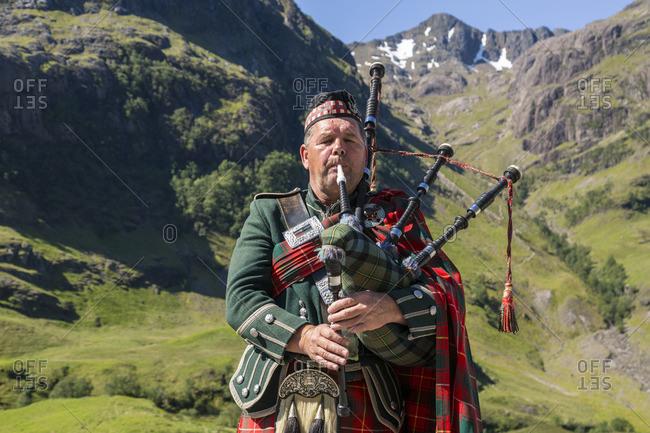 Close up of man playing bagpipes at Three Sisters mountains