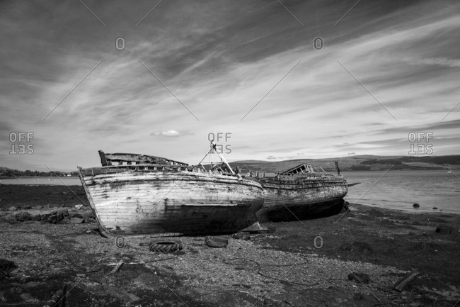 Two abandoned boat on the coast of Scotland in black and white