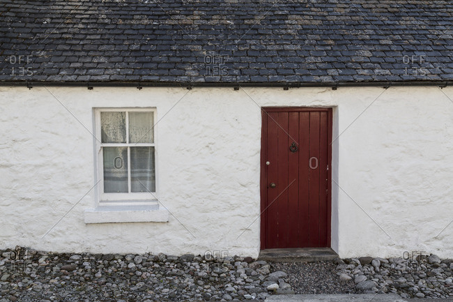 House with maroon doo in Dervaig, on the Isle of Mull, Scotland