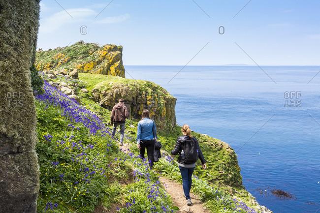 Three people hiking along the coast of Lunga Island, Scotland
